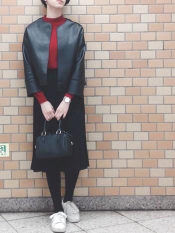 ノーカラーの品のある黒ジャケットにダークレッドのセーターの丈間が絶妙なバランス。クラシカルな装いに活かされています。足元がスニーカーなのもポイントです。