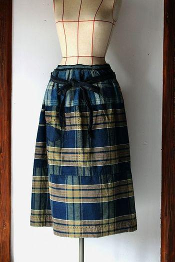 『農婦シリーズ インディゴチェックのロングスカート』  日本の古布を使用し、19世紀ヨーロッパの農婦がはいていたスカートをイメージして制作した「農婦シリーズ」。19世紀頃の藍染めチェックの木綿生地をベースに、同じく19世紀頃の野良着の中から相性の良さそうな色の木綿をパッチワークでプラス。