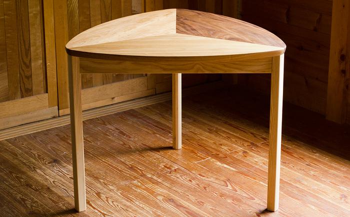 専門学校時代の先生からの「さんかくスツールのデザインに3種類の木で色分けするアイデアを加えてテーブルにしてほしい」という依頼で制作された「おにぎりテーブル」。天板が特徴的な小ぶりのテーブルです。 伸縮する無垢の板を3枚組み合わせるには工夫が必要ですが、伸縮をあえて止めず、それぞれが動けるように余裕を持たせた構造になっています。湿度によって板の隙間が開いたり閉じたりするので、実用性はやや落ちるかもしれませんが、その分無垢の木を楽しめる仕上がりになっています。