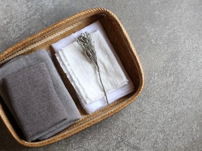 <竹かご燻製仕上げ 平かご> 平らに裂いた竹を編み上げて作られた、美しい網目が目をひく大きめサイズの平かご。落ち着きのある薄茶色に仕上がっているのは、燻製した竹を使用しているため。着替えやタオルを収納したり、来客用のスリッパを入れたり、使い勝手のよいかごです。