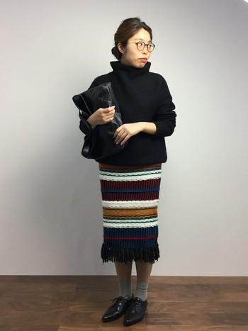 マルチカラーのボーダーが目を引くタイトなニットスカート。トップスをシンプルにすることでスカートの色や素材感が引き立っています。