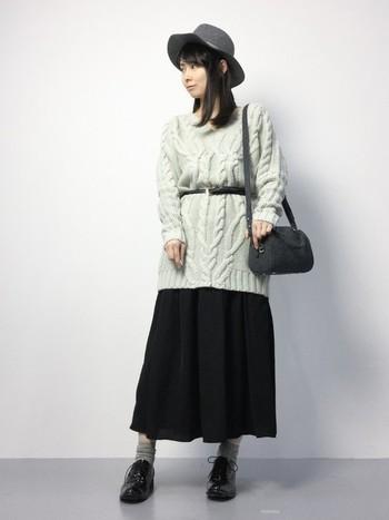 細ベルトでウエストマークしたニットワンピースにロング丈のプリーツスカートを合わせて。