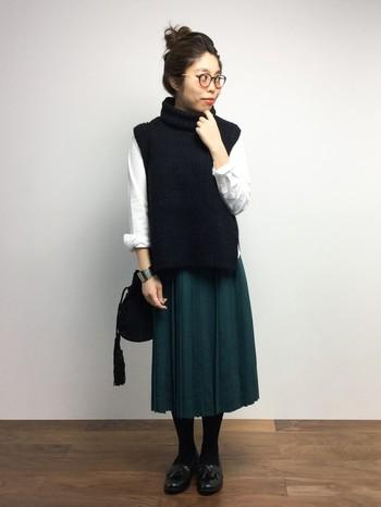 シャツ×ニットベストのセットアイテムと、綺麗な色のプリーツスカートを合わせて。白×黒×緑で、落ち着いたカジュアルさのある3色コーデの出来上がり。