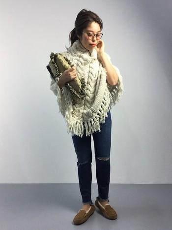 フロントのケーブル編みがポイントのポンチョは、南米ペルーのインディオたちが編みあげたハンドメイド品。たっぷりフリンジがトレンドの存在感のある1枚だから、シンプルなデニムスタイルで軽やかに。
