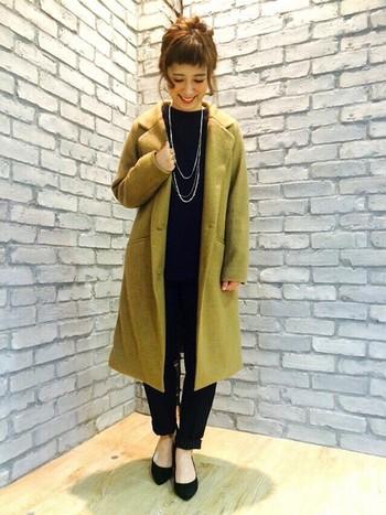 全身ブラックコーデを明るい色のコートでスッキリまとめたオシャレスタイルです。
