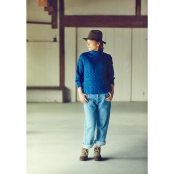 綺麗なブルーセーターとジーンズをロールアップ。ごつめのブーツも、少しだけ足首を見せて女性らしさを。