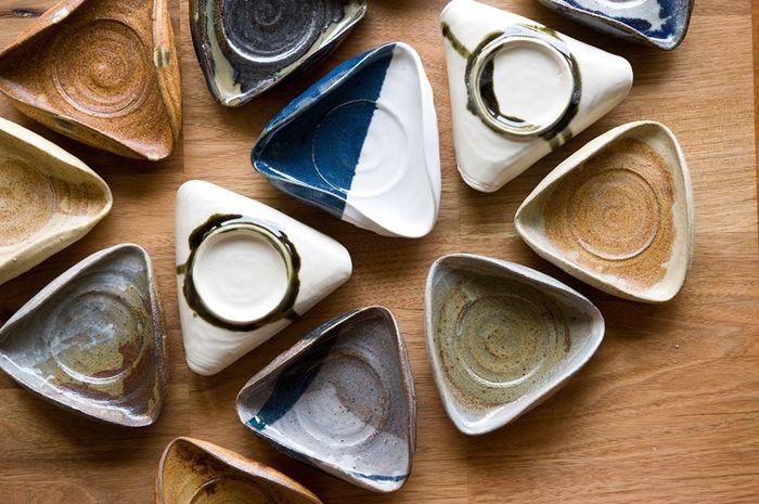 """陶芸工房SHIKI哉の中村拓哉氏とのコラボレーションから生まれた器「三角皿」。おむすびの形が素敵ですね!他に、""""山""""の形をした「山皿」もあります。"""