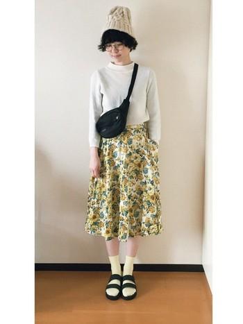 ニット帽がサンダルやショルダーのカジュアル感をお花柄のスカートとともに可愛い雰囲気に仕立て上げてくれます。イエローとブラックでまとめた上級者コーデです。