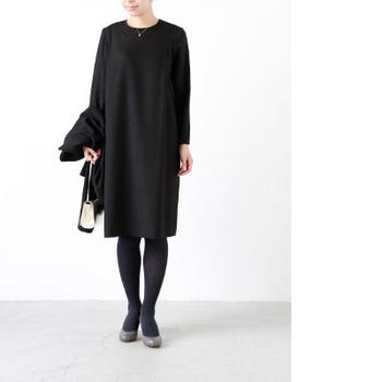 すとんと落ちたラインがきれいなブラックドレス。ひざ丈のコクーンシルエットが全体をすっきりと見せるおしゃれなデザインです。