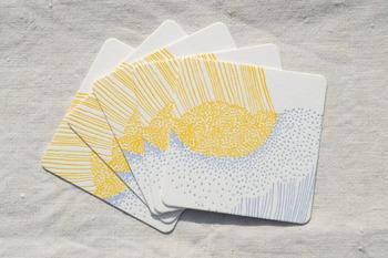 明るいブルーとイエローの配色が美しい、力強い雨が点と線で描かれた「どしゃぶり」。こちらのコースターもレタープレスによるものです。