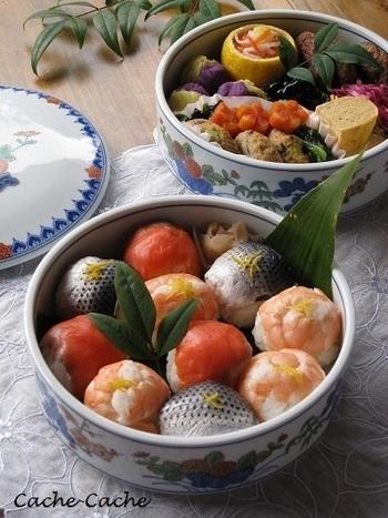銀色に光るコノシロの背や、笹の葉などの彩りで華やかに仕上げておもてなしの一品に。陶器のお重もお洒落です。