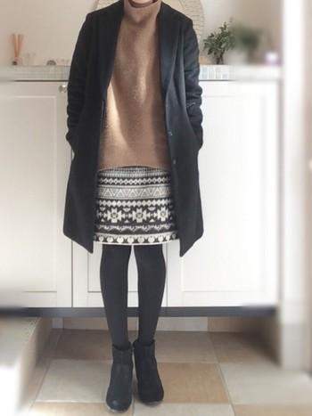オルテガ柄のスカートはインパクト大、だからこそシンプルなアイテムと合わせたいですね。キャメルのニット以外は黒でまとめているのでまとまって見えます。
