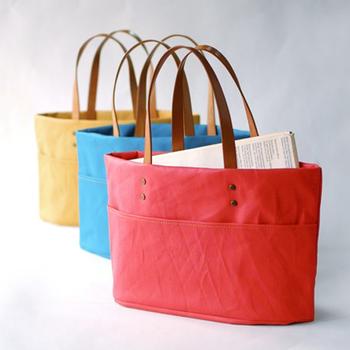 鮮やな発色が印象的なトートバッグは、丈夫な作りと広くしっかりとした底が頼もしいですね。A4雑誌がストンと入る広い口と、手にも、肩にも掛けられる使い勝手の良さが魅力です。