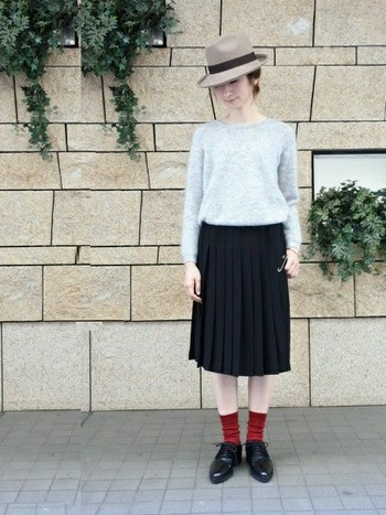 シンプルなニットとプリーツスカートのコーデに、赤のソックスを差し色でプラス。赤ソックスは、マニッシュシューズとも相性が良いですよ。