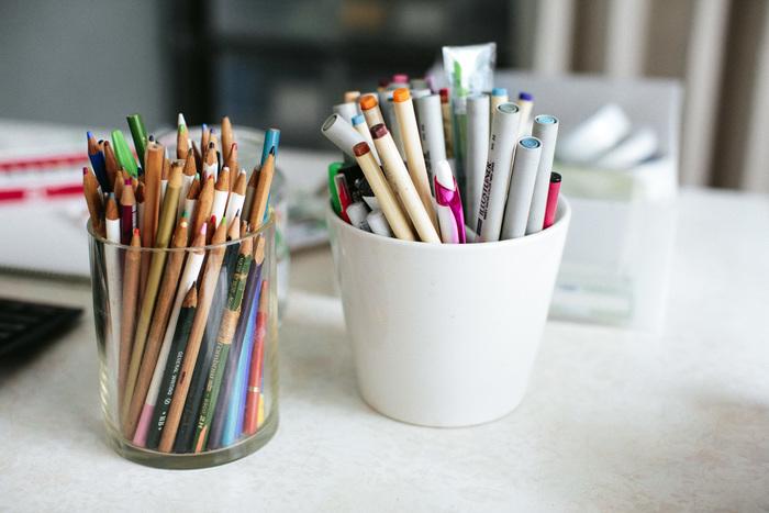 机の上には、カラーペン、色鉛筆、絵の具など、様々な画材が並びます
