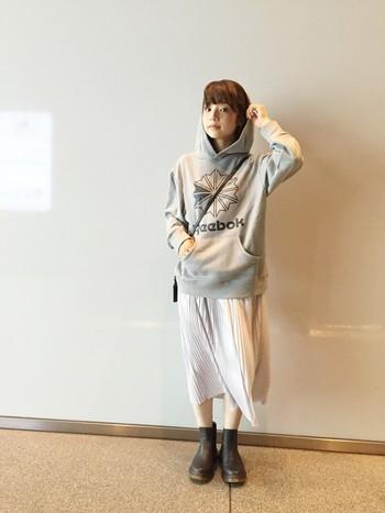 Reebokのロゴ入りスウェットに、軽やかな素材のプリーツスカートやレザーブーツを合わせた甘辛ミックスコーデ。カジュアルなのに、男女とも受けが良さそうなコーディネート。