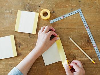 コースターやランチョンマットに丁度いい大きさの合板を用意し、マスキングテープを使って幾何学模様を作っていきます。