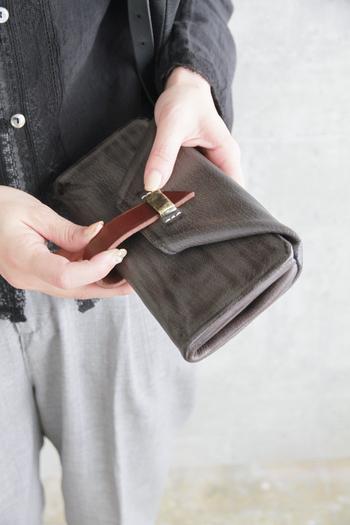 折りたたんだようなデザインが特徴的なシルエット。中央のベルトを外して開閉します。ちょっと開けにくそう・・・と思うかもしれませんが、そんなひと手間がだんだんと可愛く思えてくるお財布です。