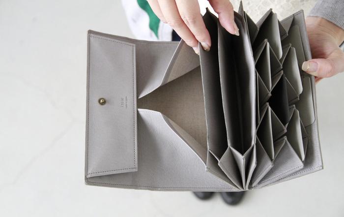 開くとジャバラのように広がる小銭入れやカードポケット。カードは縦に収納するオリジナリティ溢れるデザイン。スナップボタンが2つ付いているので、容量にあわせてサイズ調整が可能です。