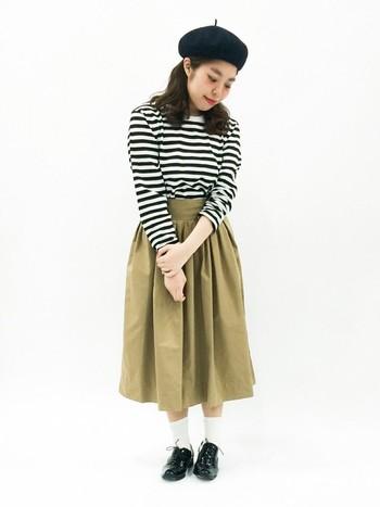 agnes b.のボーダーカットソーに、ベージュのミモレ丈スカート、ベレー帽で文学少女風の着こなし。