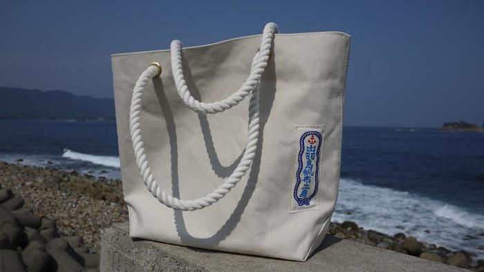 手羽島帆布工房。京都出身でサーファーでもあるオーナーの佐々木さんが、出羽島の風景、そして「いい波」に惹かれて移住。佐々木さんが作るかばんに、地元の漁師さんが作るロープを持ち手につけて、潮風が似合うこんな帆布バッグが生まれました。