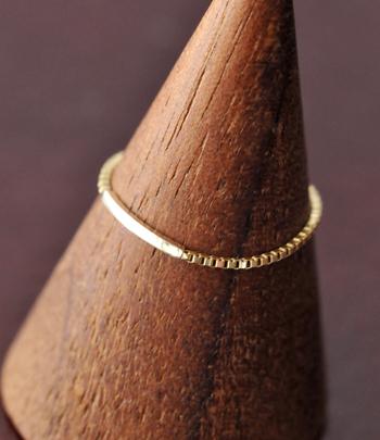 リング中央にゴールドのプレートをあしらい、細めの「キヘイ0.35チェーン」を使った繊細な手仕事が宿るリング。細見で小さなリングではありますが、確かな存在感とゴールドの美しい輝きをしっかり放っています。 プレート部分は指の形に沿って弧を描いており、チェーン部分も指へのフィット力が高いので着け心地も気になりません。