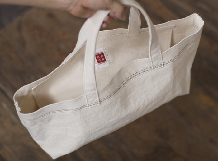 古くから綿花栽培や撚糸技術が培われ、現在でも国内最大の綿帆布の生産量を誇る岡山県倉敷市。「倉敷帆布」の製品づくりは、シャトル織機でオリジナルの生地を織り上げることからはじまります。生地の縁に出る耳「セルヴィッジ」がその証です。