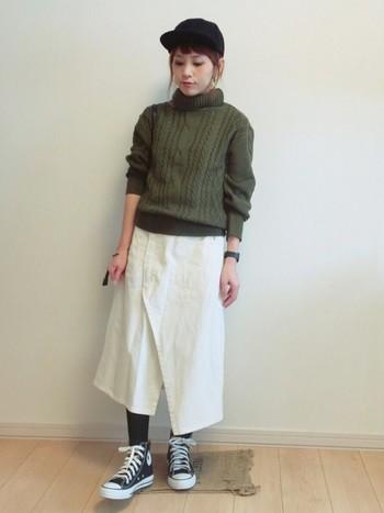 今年流行のカーキのざっくりとしたケーブルニットに、白のナチュラルなスカートが素敵。キャップとスニーカーの色を合わせるのは基本ですね。