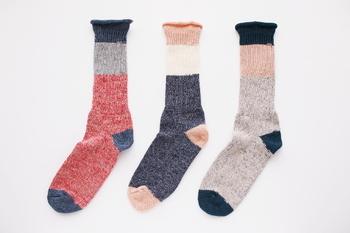 """アンゴラやカシミヤ糸を混紡したウール糸を使用した、ネップウールの""""ざっくり編みくつした""""もあります。どこか懐かしさを感じさせるレトロなデザインの靴下は、やさしく、あたたかく足を包み込んでくれます。"""