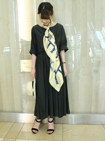シックな黒のマキシ丈ワンピースに、華やかなイエロー系の大判スカーフをコーディネート。スカーフを大胆に下に流すことでエレガントさが際立ちます。