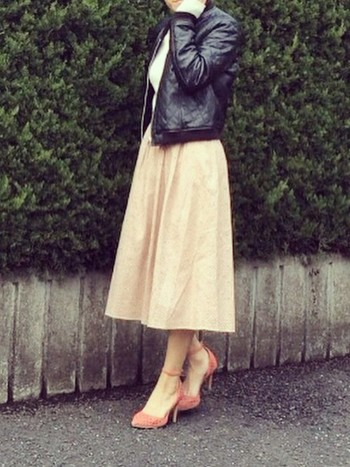 ベージュピンクのスカートの、足元もピンクの靴で女性らしく。黒のブルゾンが甘すぎないようにバランスをとっています。