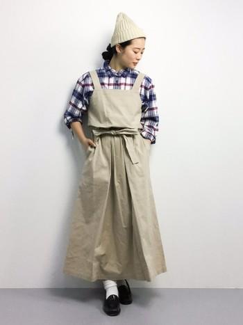 ボーイッシュなオーバーサイズのチェックシャツには女性らしくエプロン風のワンピースで女性らしさを加えて。ナチュラルなチェック柄コーデの完成です。