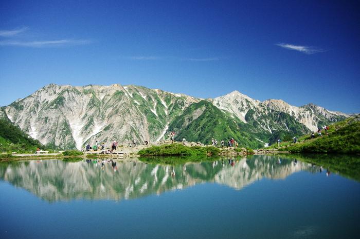 白馬連峰の唐松岳から八方尾根を辿って行くと、美しいエメラルドグリーンの水を湛えた八方池が現れます。遠くの白馬三山が鏡のように映り込み、まるで本場アルプスのような光景です。