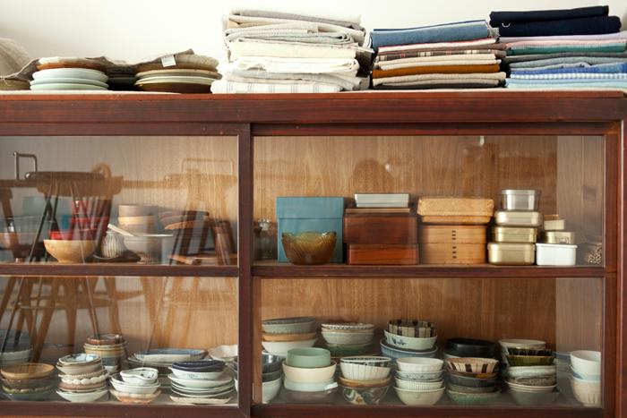 作業場に置かれたアンティークのガラス棚。中には、大小さまざま、色とりどりの器が収められています