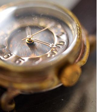 型押し真鍮文字盤腕時計です。こちらの時計はJHAに所属する女性作家enさんのハンドメイドの時計。味ある真鍮の文字盤や目を引くホワイトの針・アンティークなデザインなど、どれをとっても手造りの魅力が感じられ、長く愛用したくなる一品です。