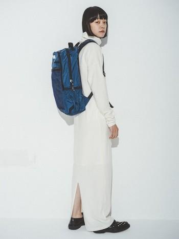 シックなホワイトのシルエットでまとまったコーディネートに、カジュアルなバッグパックを組み合わせたスタイルです。一見組み合わせに迷いそうなスタイルも、ブルーのバッグパックが差し色になった意外性のある組み合わせが絶妙なバランスを生んでいます。