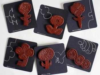 一点一点時間をかけ丁寧に磨かれた革に、繊細な草花の模様が彫られています。キュートなボタニカルモチーフたちが、レザーによってちょっぴり大人っぽく。丈夫で軽い付け心地なのがうれしいですね。それぞれのブローチに合わせて、台紙に描かれた手書きのイラストも素敵。プレゼントにぴったりです。