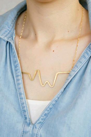 独特な波形を表現した真鍮のネックレス。存在感のあるデザインなので、胸元にきれいなアクセントが出ますね。
