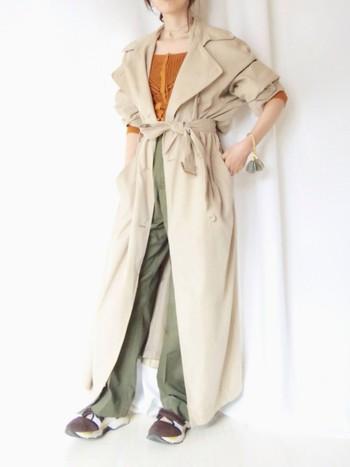 ヴィンテージのトレンチコートがかっこいいスタイル。モスグリーンのワイドパンツにオレンジのトップスが印象的。