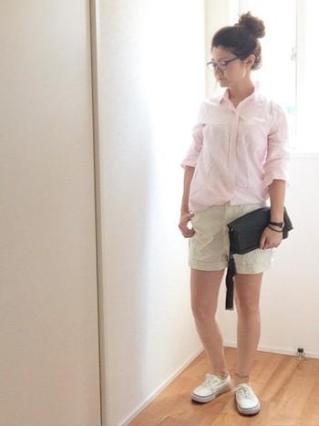 ピンクのシャツ×ベージュのショートパンツの組み合わせ。シャツをあわせれば脚を出してもイヤらしくならず、健康的な印象に。黒の小物で印象を引き締めて。