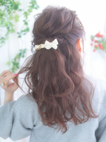 ゆるいウェーブをかけた髪のサイドを編み込んでバレッタで留めるだけ。バレッタを使うことでいつものハーフアップが華やかに。
