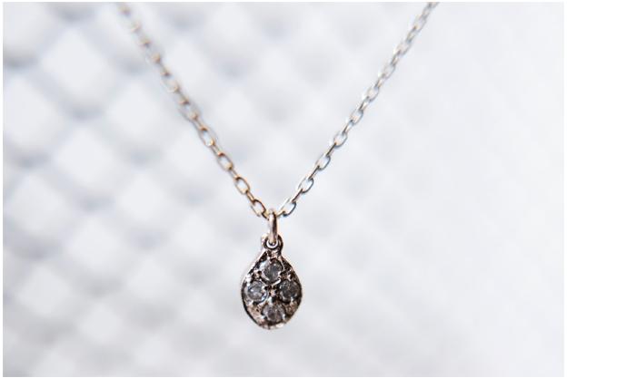 しずくの形に4粒のホワイトダイヤがはめこまれたネックレス。 石のように凹凸のあるゴールドのテクスチャーが落ち着いた雰囲気を作っています。