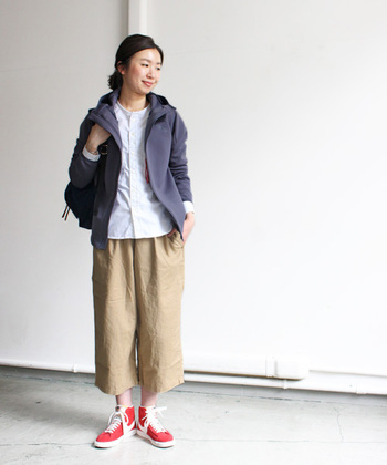 濃いグレーのジャケットが、白とベージュの組み合わせを引き締めます。素材感の違いが、大人なスタイル。