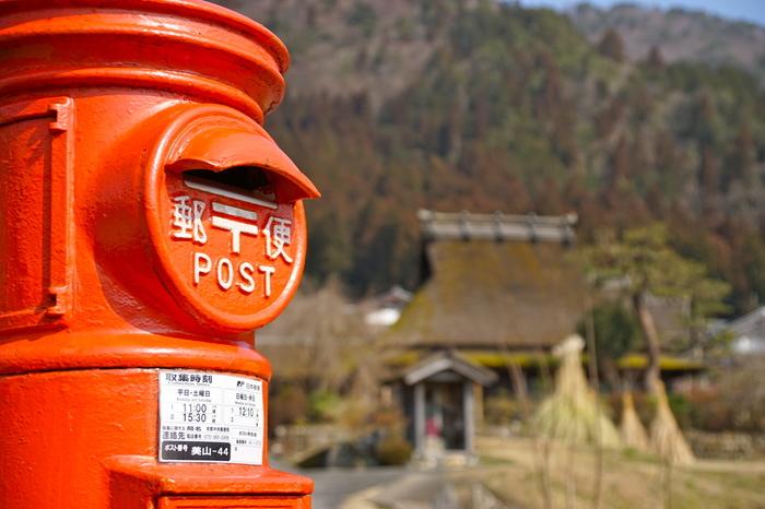 都心部では珍しくなった、丸型の赤いポスト。見る者を懐かしい気分にさせてくれるポストが、古き良き日本の伝統を受け継ぎながら生活が営まれている「かやぶきの里」の魅力を引き立てています。
