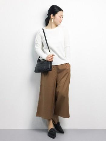 白トップスとワイドパンツのシンプルなコーディネートも、黒のポシェットとパンプスできれいめに着こなせます。