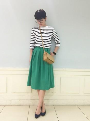 カジュアルなボーダーカットソーを、爽やかなグリーンのスカートとパンプスと合わせて上品にまとめたコーディネートです。春らしい明るめカラーのポシェットをアクセントに。