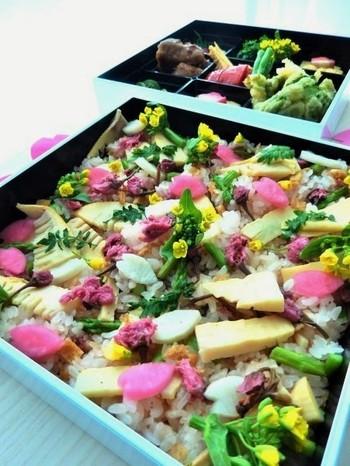 タケノコや菜の花など、春の味覚がたっぷり入ったおこわです。花びら型に型抜きした甘酢の大根と梅酢のカブがアクセントに。