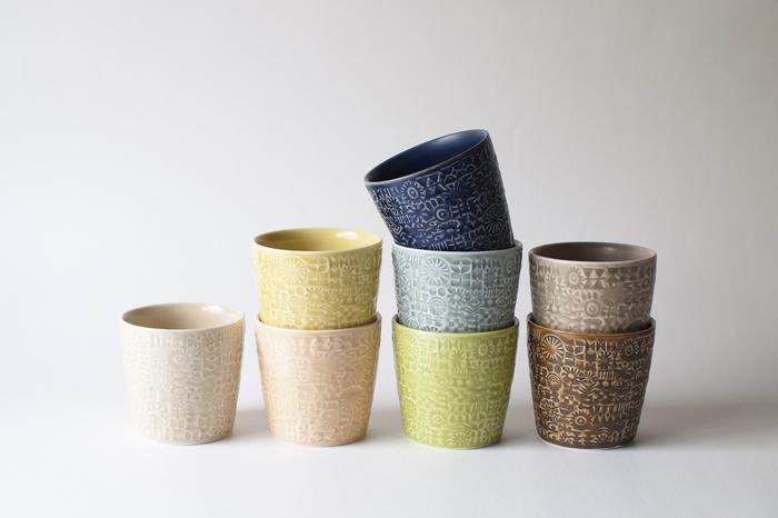 """鳥や花の愛らしいパターンに目を奪われる「PATTERNED CUP」。  カップの表面に隙間なく施された模様は、伊藤さんが自作の小さな""""はんこ""""を陶土に押してできたもの。 手触りも心地よく、凸凹によって生まれる色の濃淡も楽しめます。"""