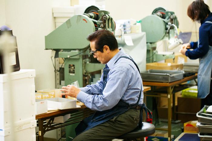 「土屋鞄製造所」創業者の土屋國男さん。ランドセルに使用される小さなパーツの一つ一つを、角度を変えて丁寧に検品していきます