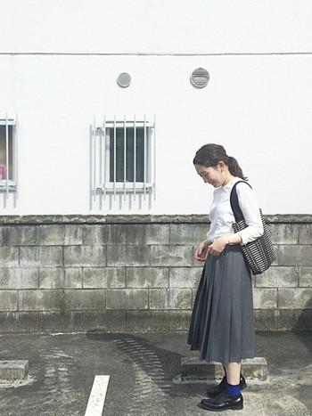 白シャツとグレーのプリーツスカートを合わせた、クラシカルなコーディネート。ブルーの差し色で、ちょっぴり遊びゴコロを取り入れて。